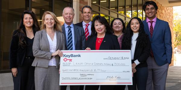 A group of professionals and students poses with a check from KeyBank to support diversity initiatives at Leeds.
