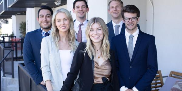 Four male and two female students pose as a group in professional dress.