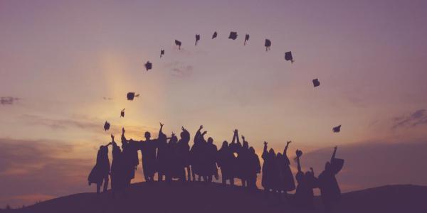 alumni throwing grad caps in air