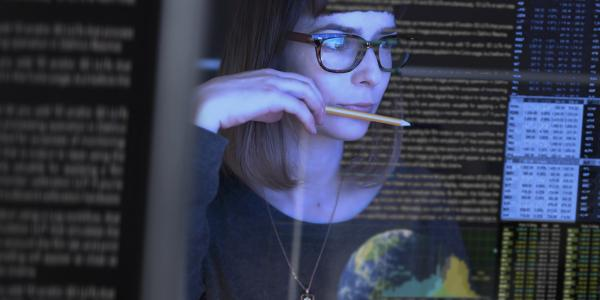 Image of woman looking at code on a screen