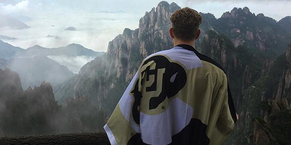 Education abroad student holding a CU flag