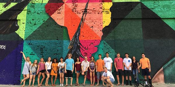 Global programs students standing in front of a painted mural in South Africa