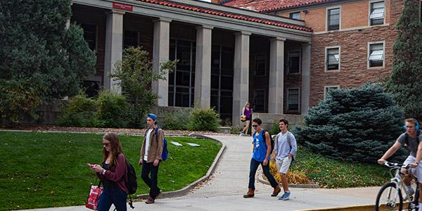Undergraduate business school students walking by the Cheyenne arapaho building