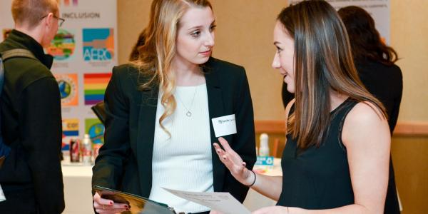 a business school student engaged with a corporate partner at a recruitment event