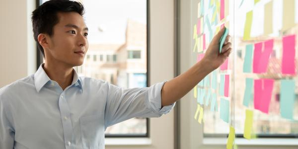 man pointing to post-it notes on wall