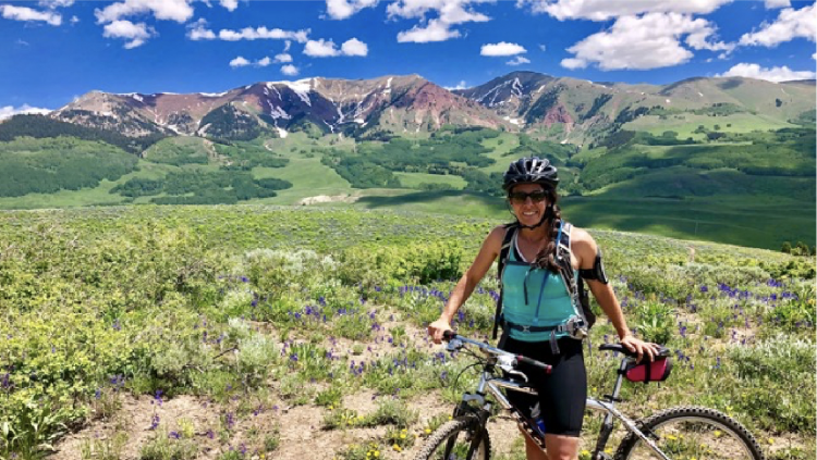 photo of Brittney with her bike, in front of a canyon