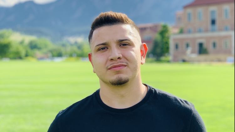 Headshot of David Lopez outside on the lawn by Koelbel, Flatirons in the background