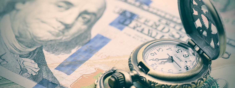 A vintage pocket watch opened upon a stack of hundred-dollar bills.