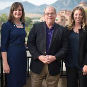 Four women surround Mark Meaney in a professional photo in front of the Flatirons.