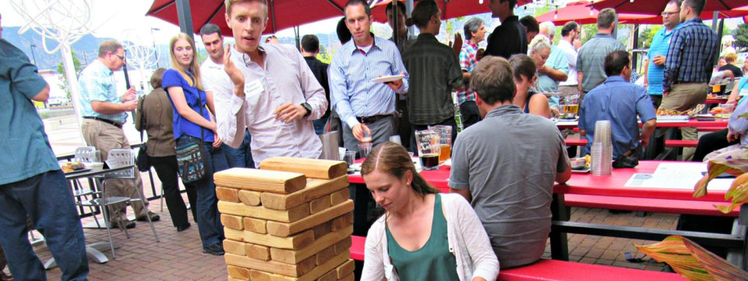 attendees at happy hour event, enjoying social event, with food and giant Jenga