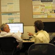 instructor assisting a student at a computer screen