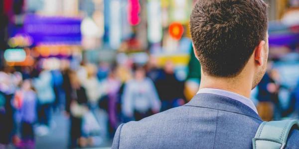 Photo of man in suit walking across street