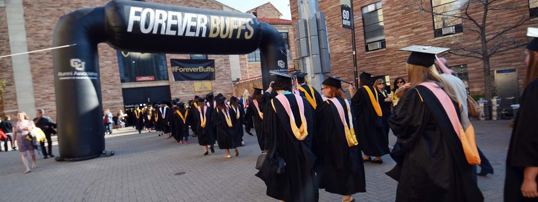 graduates walking under forever buffs banner