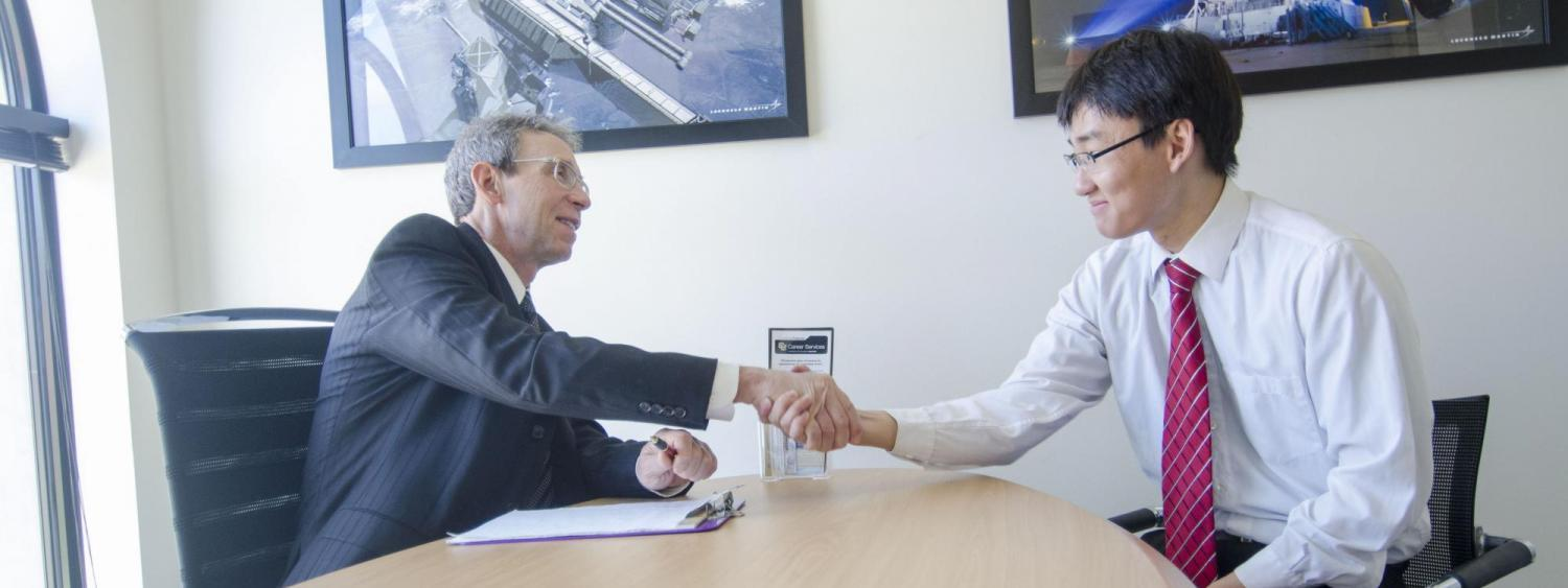 Student wearing a white button up and red tie shaking hands with a businessman in a blue suit at a CU Boulder Career Services office