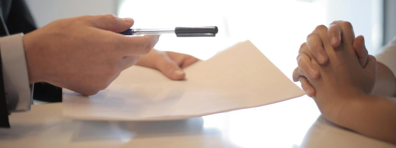 two people talking over a piece of paper