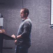 Man at podium teaching with powerpoint presentation behind him