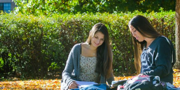 two female students talking sitting on campus