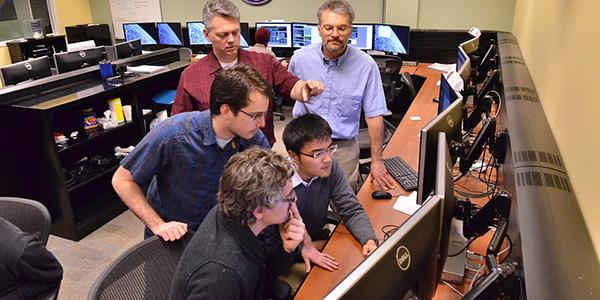 professors giving instructions to students in a computer lab