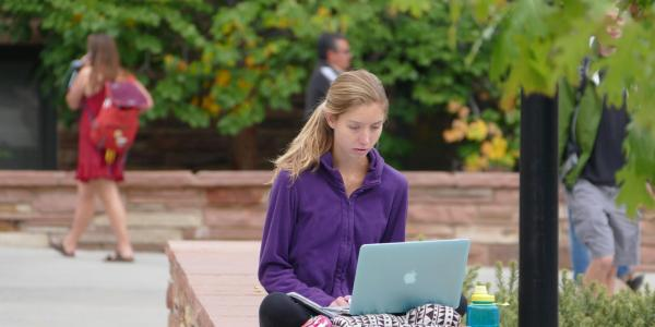 Student and computer on campus