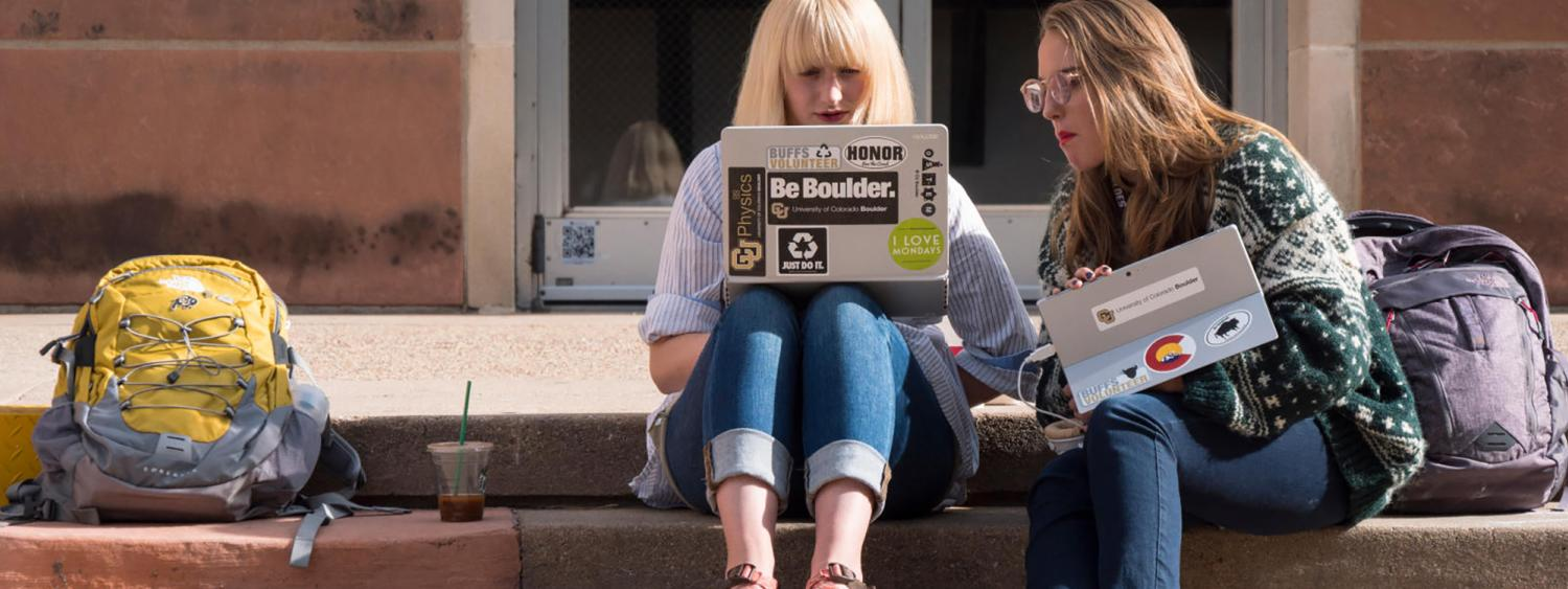 two female students looking at a computer