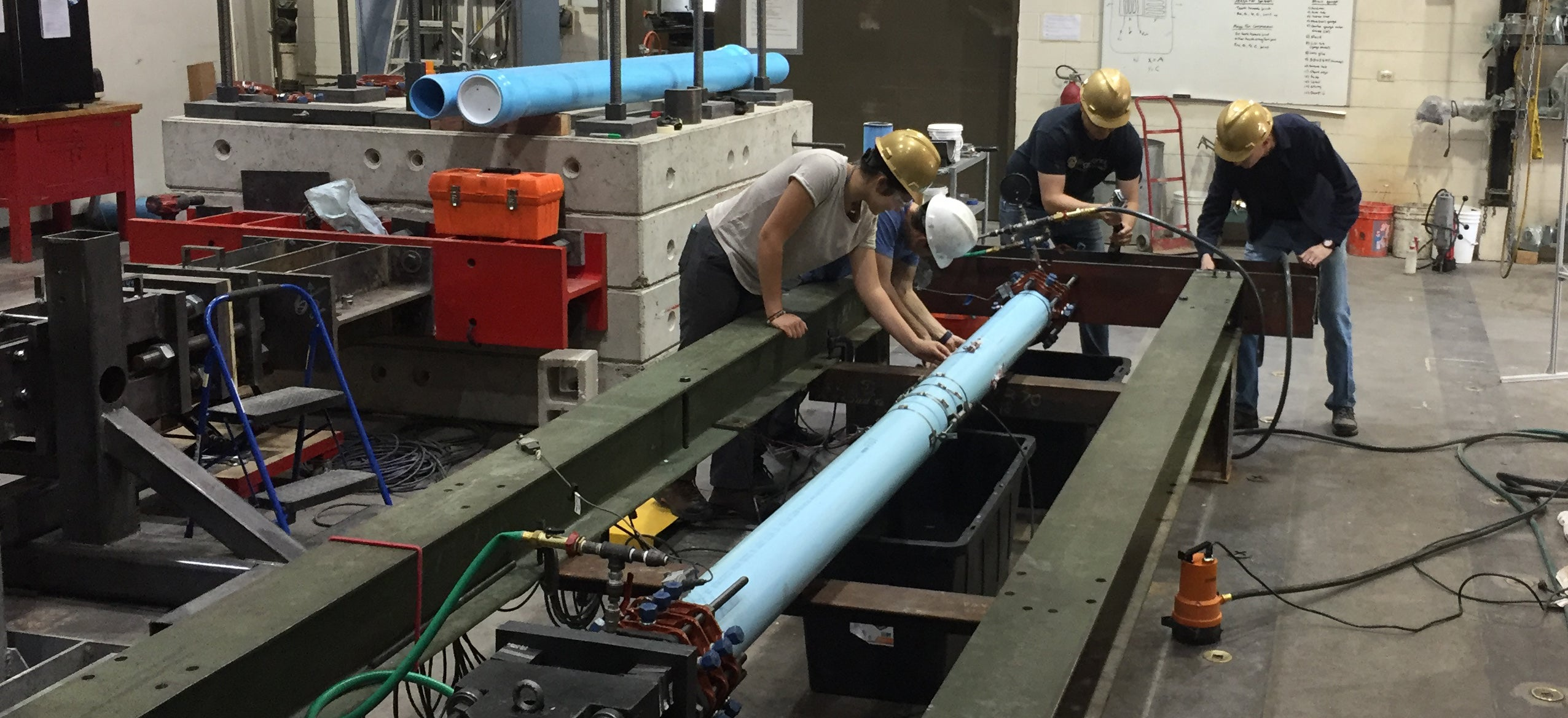 Researchers work on a pipe testing project in the CIEST lab