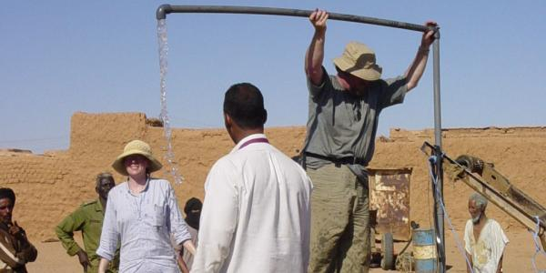 Volunteers and residents work on a water system in Mauritania