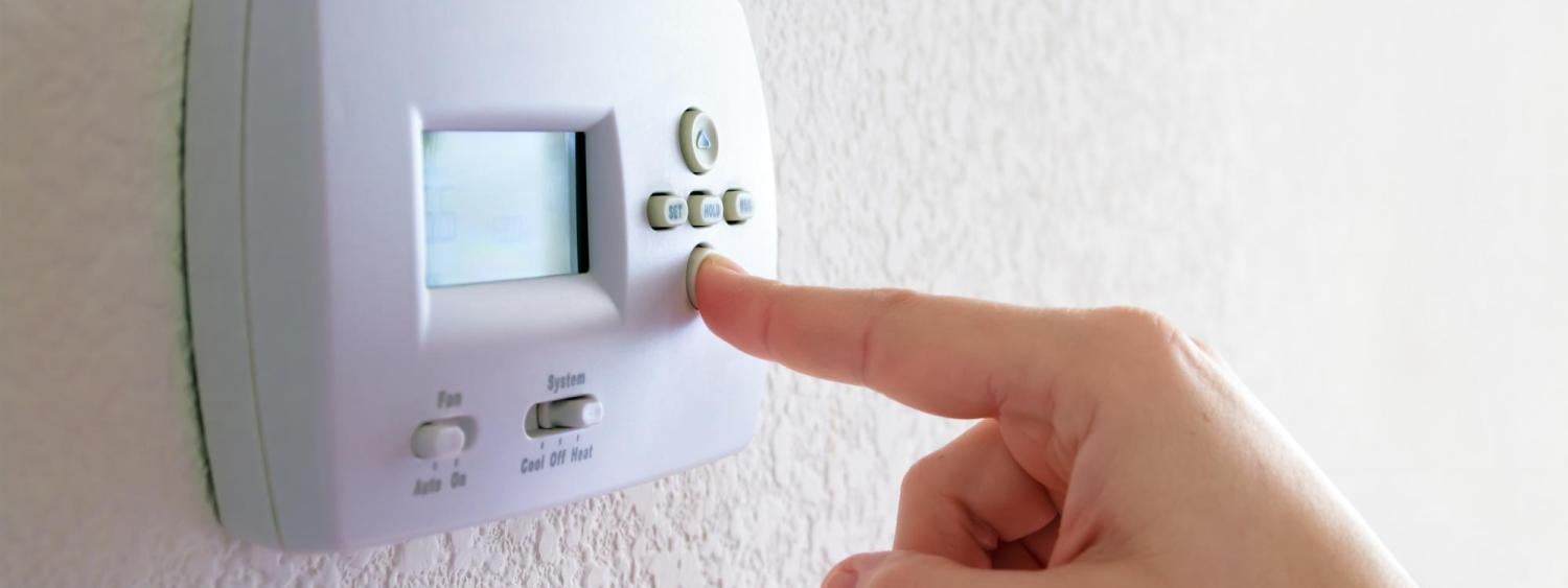 Close-up of a hand adjusting a home thermostat.