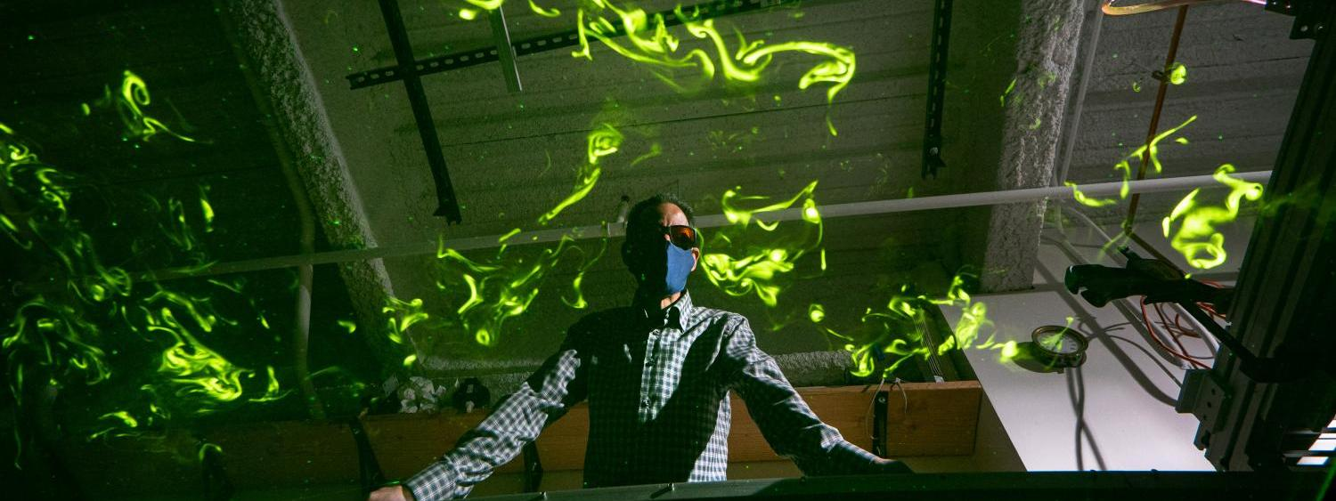 John Crimaldi watches as green laser light illuminates plumes in his lab's test flume.