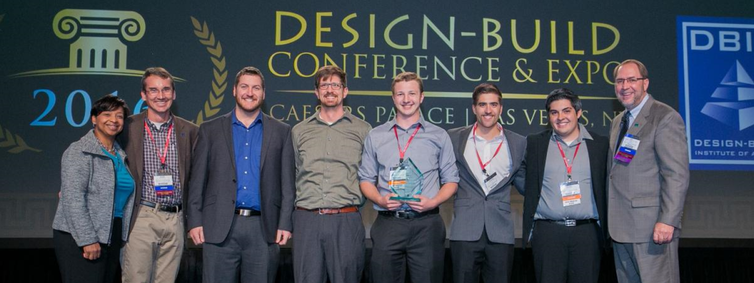 The team receives their trophy on stage at the Design-Build Conference