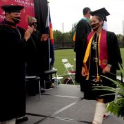 A student crosses the stage to receive her diploma during the graduation ceremony at CMU