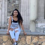 Briana Santa Ana sits atop a stone wall