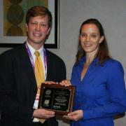 Sara Beck and an AEESP member hold the plaque Beck received to commemorate her dissertation award.