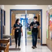 CU Boulder alumna Halle Sago, left, and undergraduate student Ricardo Reyes, right, visit High Peaks Elementary School in Boulder, Colorado, to monitor air quality. (Credit: Glenn Asakawa/CU Boulder)
