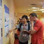 Shang Liu discusses his research with a conference attendee