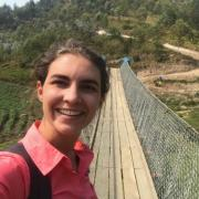 Sally Gerster takes a selfie in front of a Bridges to Prosperity footbridge in Rwanda.