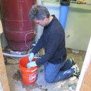 Researcher Joe Ryan collects water samples in Lafayette, Colo.