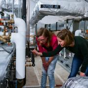 Two students checking the temperature and pressure settings for a rooftop HVAC unit in the Larson Laboratory.