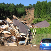 A car sits mired in the mud next to a destroyed building in a Japanese town where earthquakes triggered mudslides