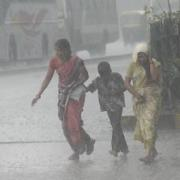 Two Indian women and a child cross a street in a driving downpour.