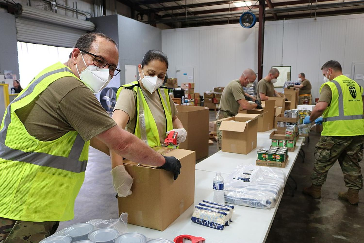 People with masks on organizing food at a food bank.