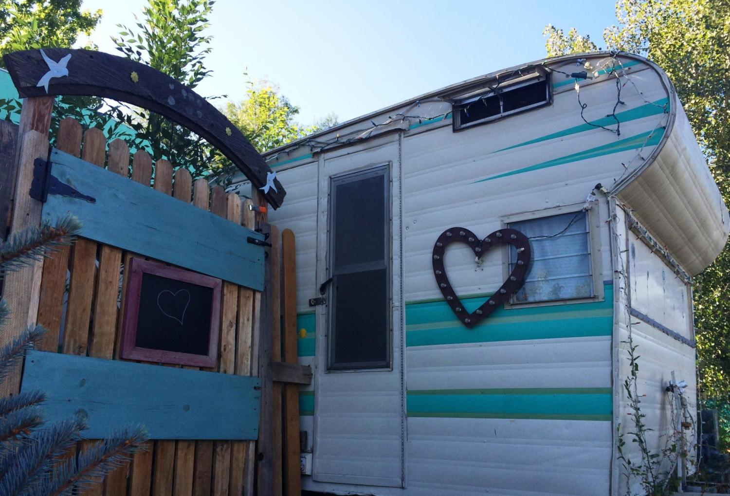 An older RV with a heart on it next to a wooden fence.
