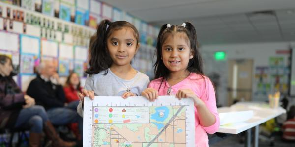 Two young students hold a draft of the child-friendly map