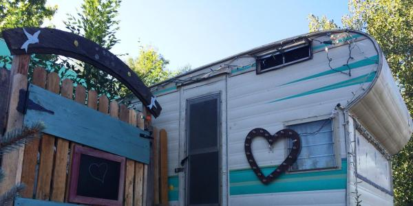 RV with a heart on it next to a nice wooden fence.