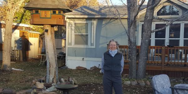 Peggy Kuhn stands in her back yard with her manufactured home behind her.