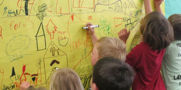 Children drawing with markers their vision of a town on paper pinned to the wall.