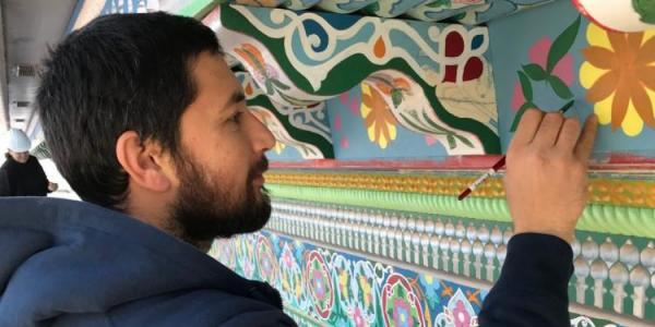 Maruf painting and restoring the trim of the Boulder Dushanbe Teahouse