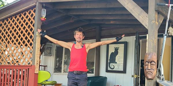 Dave Weil with arms outstretched on his porch of his manufactured home
