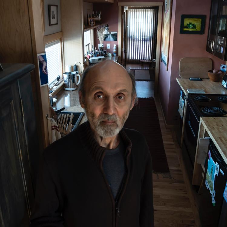 Tom Sudrow Lewis stands in his kitchen
