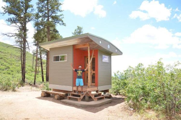 Student in front of tiny house Lama project in New Mexico, built by students.