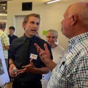 Carson Byerhof explains his poster to an attendee